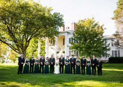 wedding party group in front of beautiful mansion
