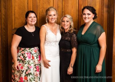 bride and friends in front of wooden doors