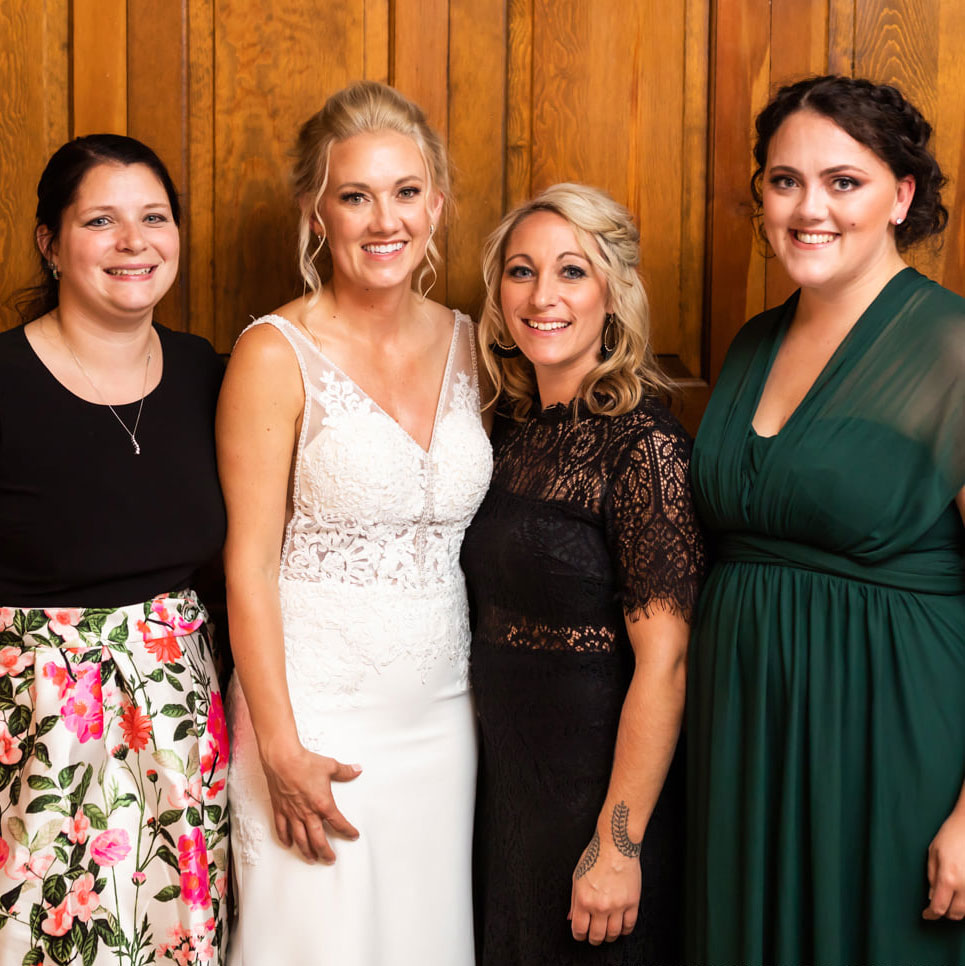 bride and friends in front of wooden doors