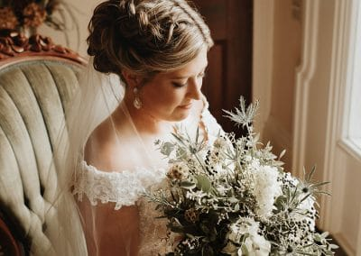 beautiful bride sitting down with bouquet