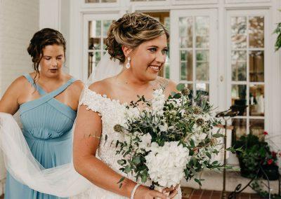 smiling bride walking with bridesmaid behind
